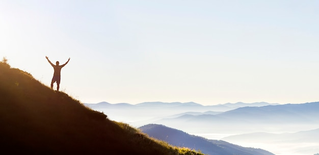Panorama de joven exitoso hombre caminante silueta brazos abiertos en el pico de la montaña.