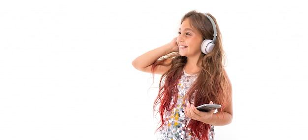 Panorama de niña con grandes auriculares blancos escuchando música, tocando su auricular derecho y sosteniendo un teléfono inteligente negro aislado