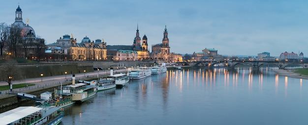 Panorama nocturno del casco antiguo de dresde con reflejos en el río elba y barcos de pasajeros