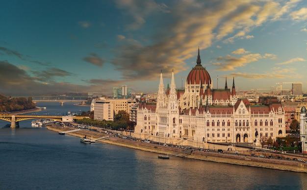 Panorama del paisaje del edificio del parlamento de budapest en la vista del atardecer con el río danubio, capital de hungría