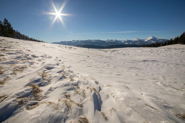 Panorama del paisaje de invierno con colinas nevadas, montañas blancas distantes, bosque oscuro y cielo azul claro con sol brillante.