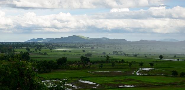 Panorama del paisaje con vista del campo verde y montañas en día lluvioso