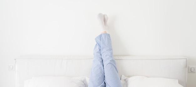 Panorama de piernas femeninas levantadas en la cama en el dormitorio