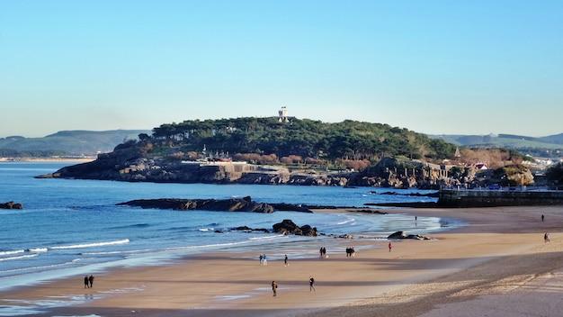 Panorama de una playa de arena con una cadena montañosa y un bosque tropical