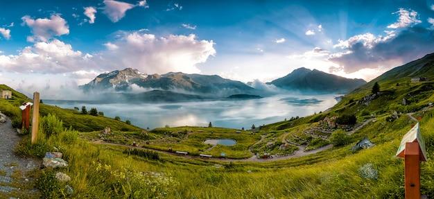Panorama en un prado en un lago de montaña durante el verano