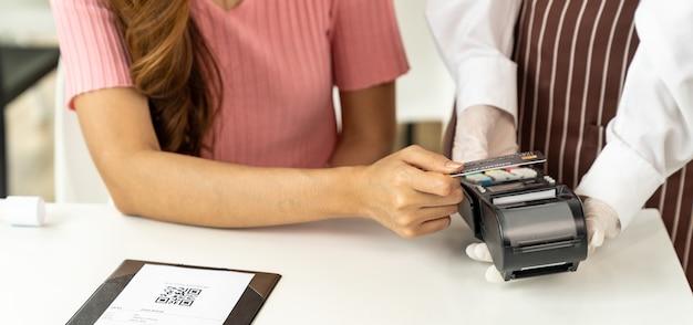 Panoramic close up cliente mujer asiática realiza pago con tarjeta de crédito sin contacto después de comer en un nuevo restaurante a distancia social normal para reducir el contacto. concepto de tecnología y sin contacto en línea.