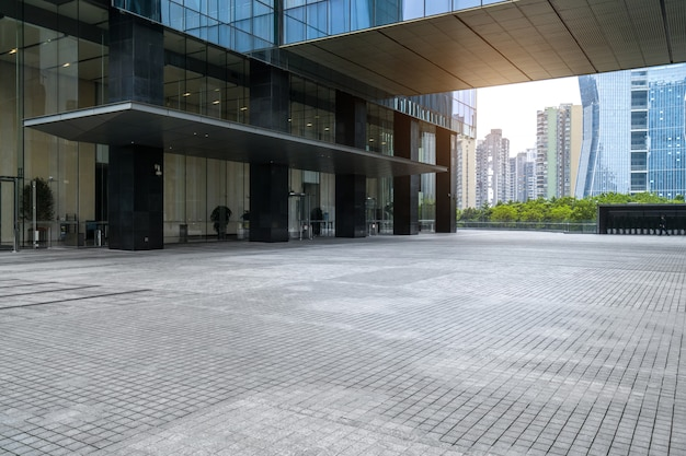 Panorámica del horizonte y edificios con piso cuadrado de concreto vacío.