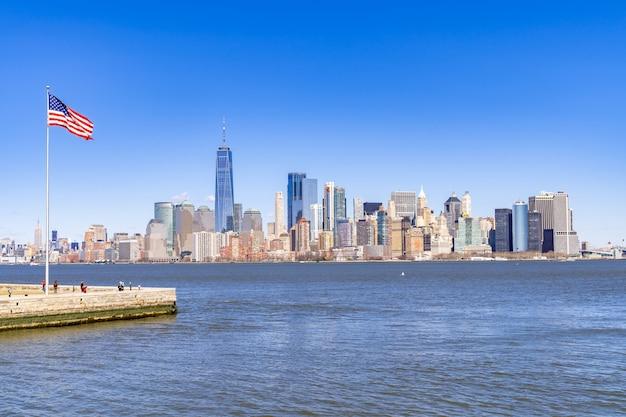 Panorámica de manhattan en nueva york y la bandera de estados unidos