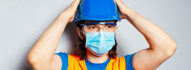 Panorámica retrato de banner de joven confiado con máscara médica en la cara, ingeniero trabajador de la construcción con equipo de seguridad sobre fondo texturizado de gris. prevención contra el coronavirus.
