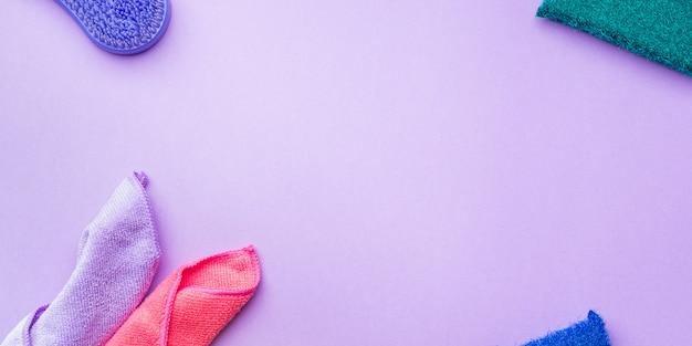 Paños de limpieza y esponjas sobre fondo de color