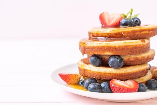 Panqueque con arándanos frescos, fresas frescas y miel