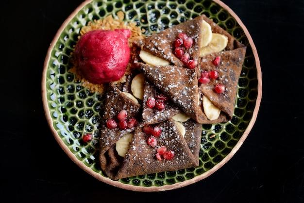 Panqueque de chocolate con plátanos, granada y sorbete