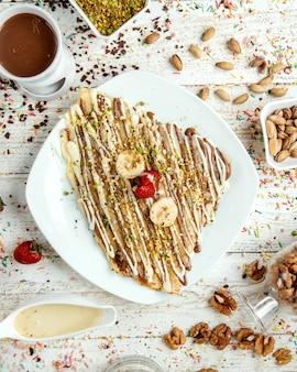 Panqueque cubierto con jarabe de chocolate y espolvoreado con pistachos rallados