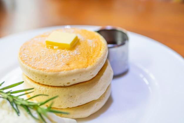 Panqueque con mantequilla derretida y almíbar encima.