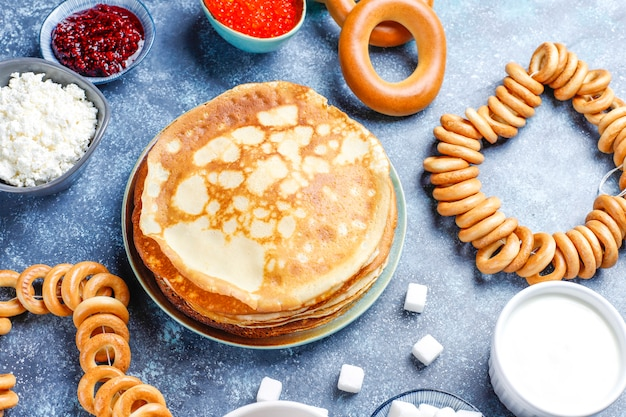 Panqueque ruso blini con mermelada de frambuesa, miel, crema fresca y caviar rojo, terrones de azúcar, requesón, bubliks en la oscuridad