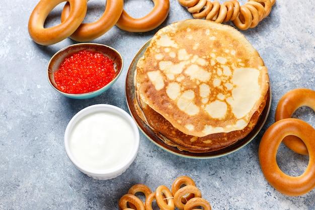 Panqueque ruso blini con mermelada de frambuesa, miel, crema fresca y caviar rojo, terrones de azúcar, requesón, bubliks