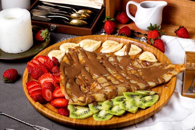 Panqueque vertido con chocolate líquido con fruta