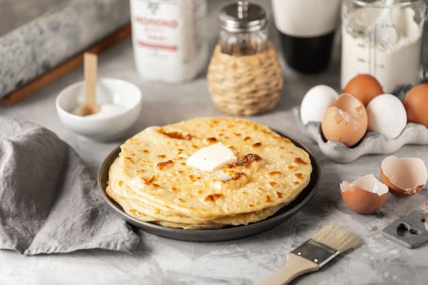 Panqueques apilados en un plato con cáscaras de huevo y una botella de leche