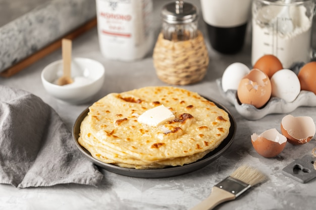 Panqueques apilados en un plato sobre una mesa blanca con una taza de café y una botella de leche