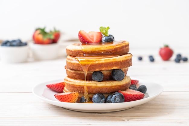 Panqueques con arándanos frescos, fresas frescas y miel.