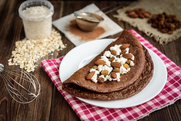 Panqueques de avena con chocolate casero con requesón en plato blanco sobre mesa de madera oscura.