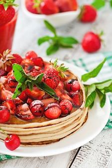 Panqueques con bayas y batido de fresa en un estilo rústico