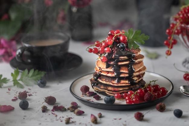 Panqueques con bayas y chocolate sobre un fondo claro con un ramo de rosas rojas. foto oscura