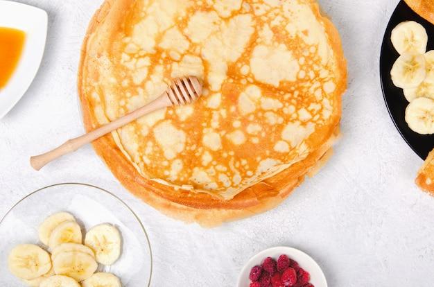Panqueques con bayas y miel para el desayuno en la mesa blanca