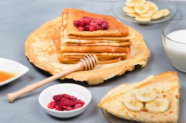 Panqueques con bayas y miel para el desayuno en la mesa gris blanco
