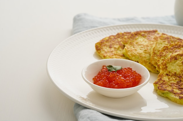 Panqueques de calabacín con patata y caviar rojo, vista lateral de dieta keto fodmap closeup
