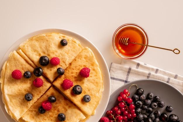 Panqueques caseros apetitosos calientes con bayas frescas maduras, grosellas rojas y moras en un plato y un pequeño recipiente de vidrio con miel en la mesa