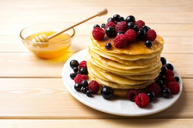 Panqueques caseros con miel y bayas frescas.