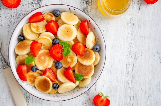 Panqueques de cereal, mini panqueques en un bol con fresas frescas, arándanos y miel. comida de moda. horizontal, vista superior, espacio de copia.