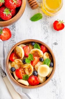 Panqueques de cereales, mini panqueques en un cuenco de madera con fresas frescas, arándanos y miel.