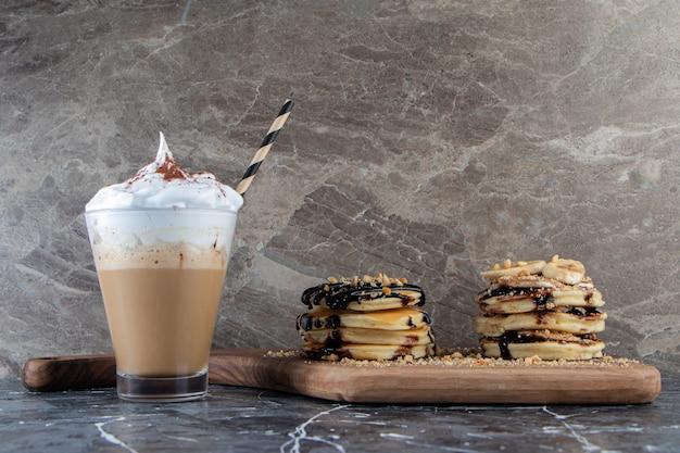 Panqueques con cobertura de plátano y chocolate sobre tabla de madera con delicioso café.