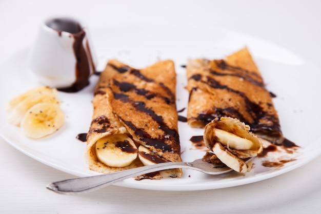 Panqueques con cobertura de plátano y chocolate.