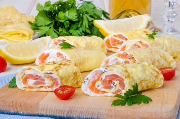 Panqueques (crepes) con salmón ahumado, queso crema y hierbas sobre superficie de madera blanca