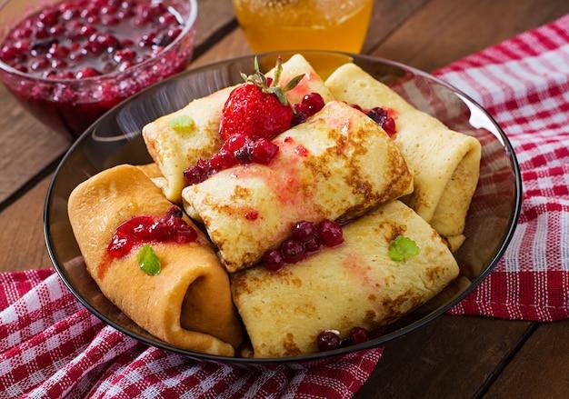 Panqueques dorados con mermelada de arándanos y miel en un estilo rústico. vista superior
