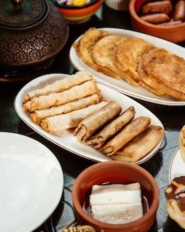 Panqueques enrollados con picatostes y queso sobre la mesa
