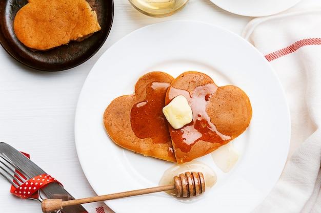 Panqueques en forma de corazón sobre un fondo claro. el concepto de un desayuno festivo para el día de san valentín o una sorpresa agradable para un ser querido