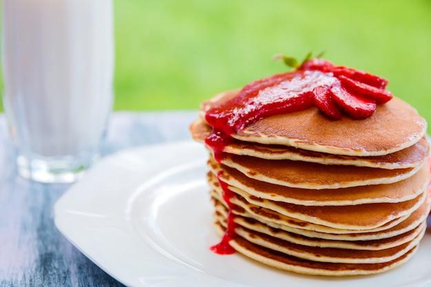 Panqueques con fresa fresca y mermelada cerca del vaso con leche