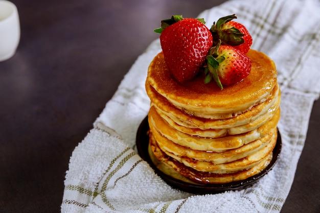 Panqueques con fresas, bayas y jarabe en un plato