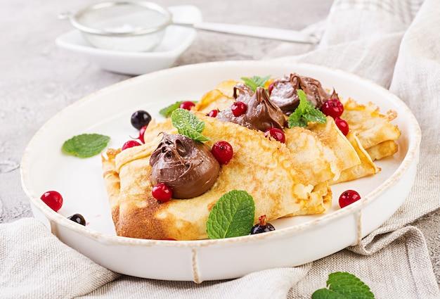 Panqueques con fresas y chocolate decorado con hojas de menta. desayuno sabroso
