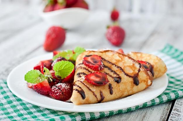Panqueques con fresas y chocolate decorado con hojas de menta