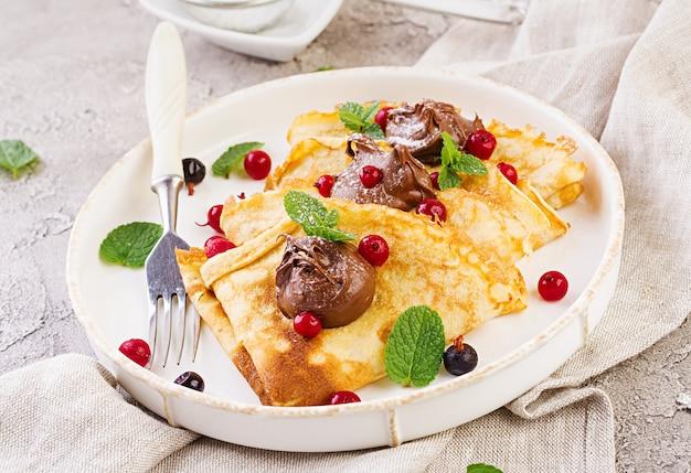 Panqueques con fresas y chocolate, decorados con hojas de menta