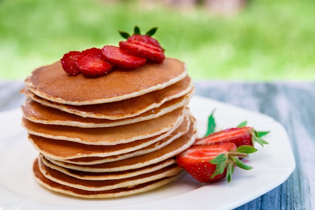 Panqueques con fresas frescas y menta en plato blanco en jardín de madera rosa o en la naturaleza. pila de panqueques en la mesa.