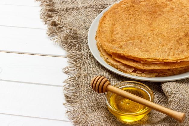 Panqueques fritos con miel en la mesa de madera vieja. vista superior