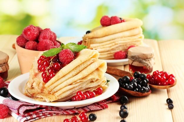 Panqueques con frutos rojos, mermelada y miel en mesa de madera