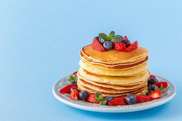 Panqueques con frutos rojos sobre un fondo pastel brillante