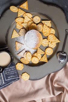 Panqueques y galletas saladas de vista lejana superior con taza de leche negra sobre el fondo gris, comida crujiente para el desayuno de galletas